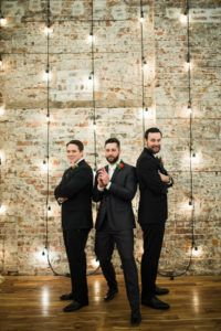 Groom And Groomsmen Brick Wall With Hanging Lights
